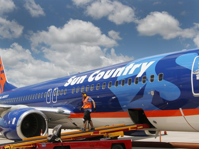 A baggage handler finishes loading Sun Country Airlines