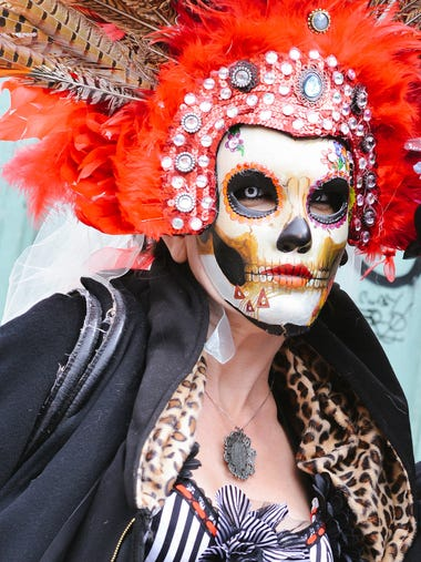 "A ""Day of the Dead"" mask adds mystery to a paradegoer"
