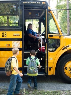 Students board a school bus in this file photo provided by the St. Johns County School District.