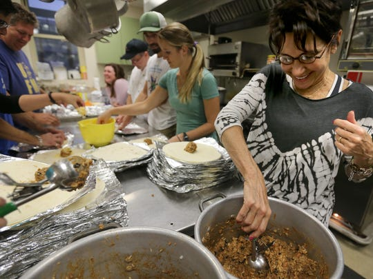 Denise Linebarier, right, helps to prepare burritos that will feed the homeless in Memphis. The Urban Bicycle Ministry takes food to the homeless and hungry on the street.