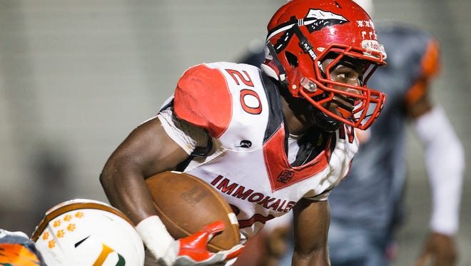 Immokalee High School's Shedro Louis breaks free from Dunbar defenders during second quarter play Friday at Dunbar High School in Fort Myers.