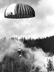 A Forest Service smokejumper descends toward a forest fire in Montana in the 1960s.