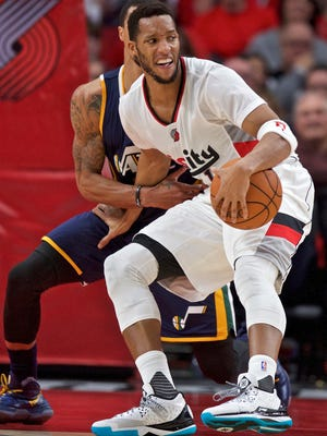 Portland Trail Blazers guard Evan Turner, right, spins around Utah Jazz guard George Hill, left, during the second half of an NBA basketball game in Portland, Ore., Tuesday, Oct. 25, 2016. (AP Photo/Craig Mitchelldyer)