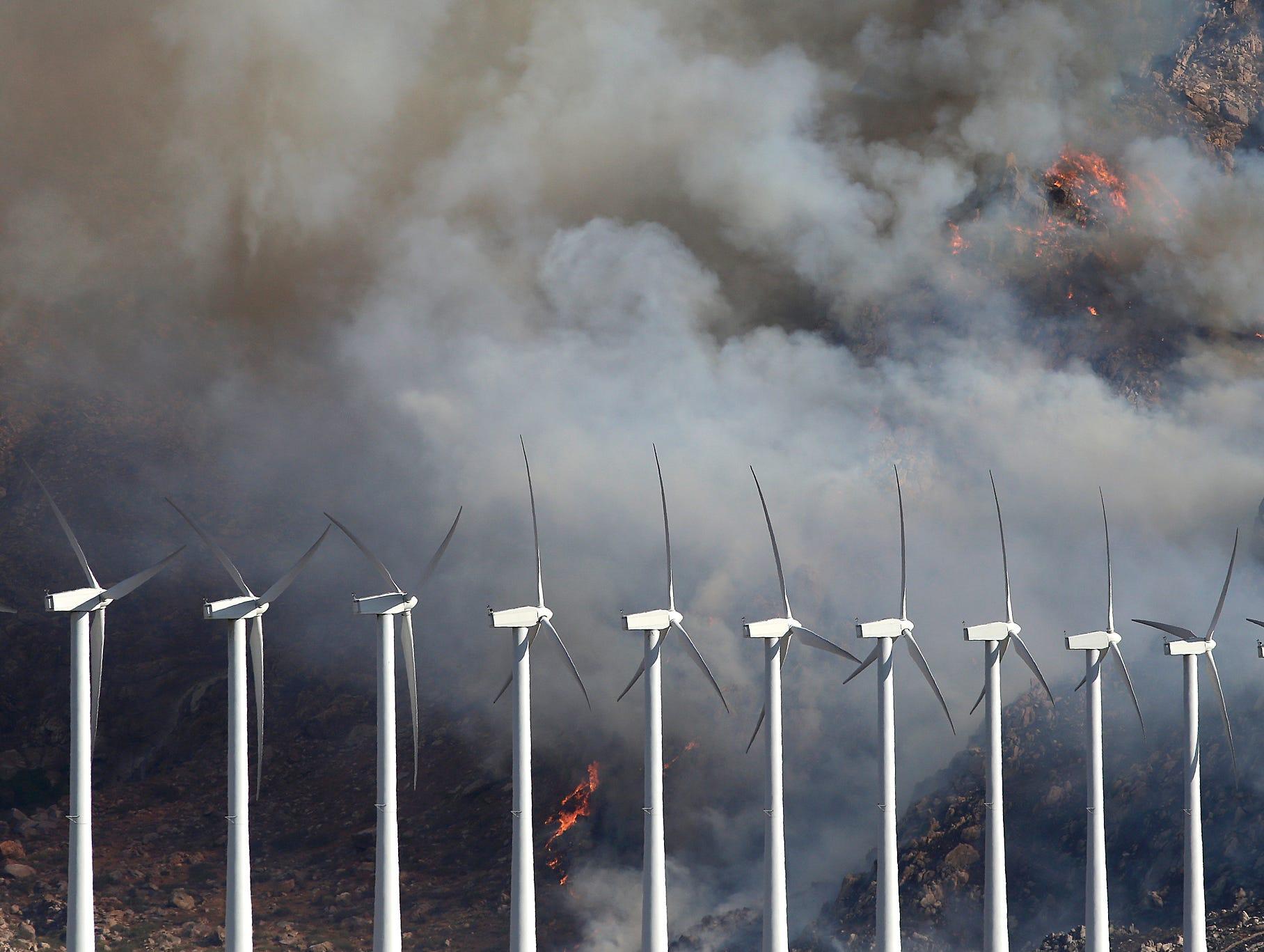A wildfire burns near wind turbines near Cabazon.