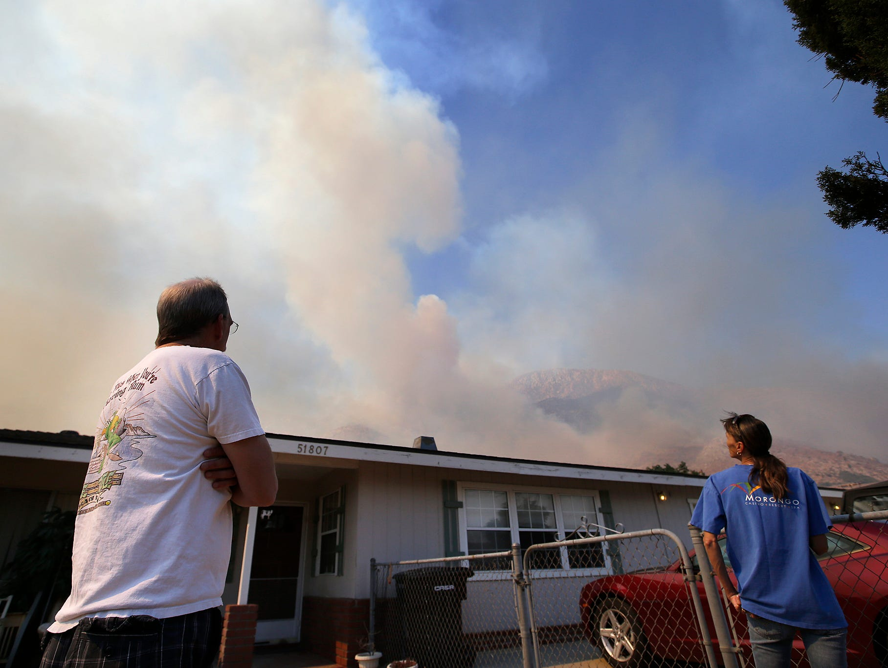 Pete Gould, left, and his wife, Angel, watch smoke rise from a wildfire in Cabazon.