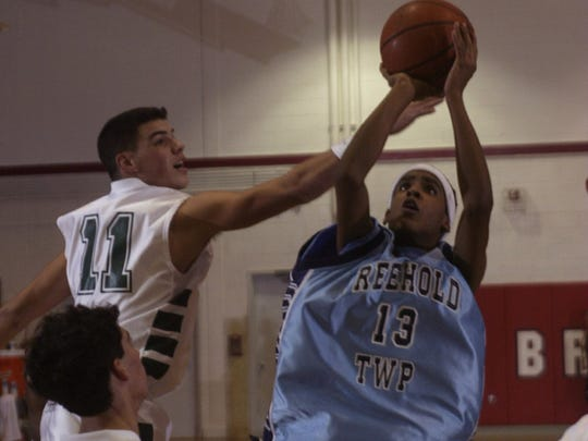 Freehold Township's Manny Ubilla goes up with shot as Colts Neck's Lou Beninato defends.