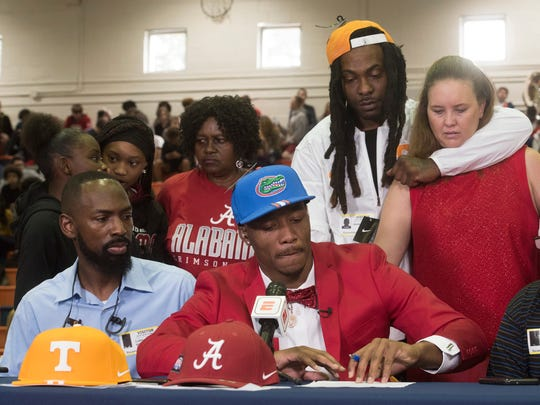 Escambia High School's Jacob Copeland, center, is surrounded by family as makes his decision to go to the University of Florida on National Signing Day during a televised event in the school's gym, Wednesday, Feb. 7, 2018.
