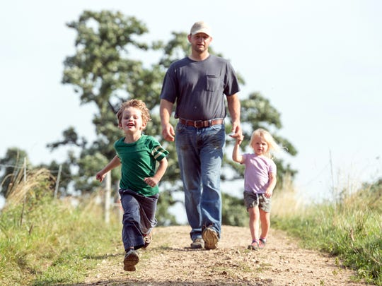Isaac Campbell takes a stroll on the farm with his son, Coy, and daughter, Wynn.