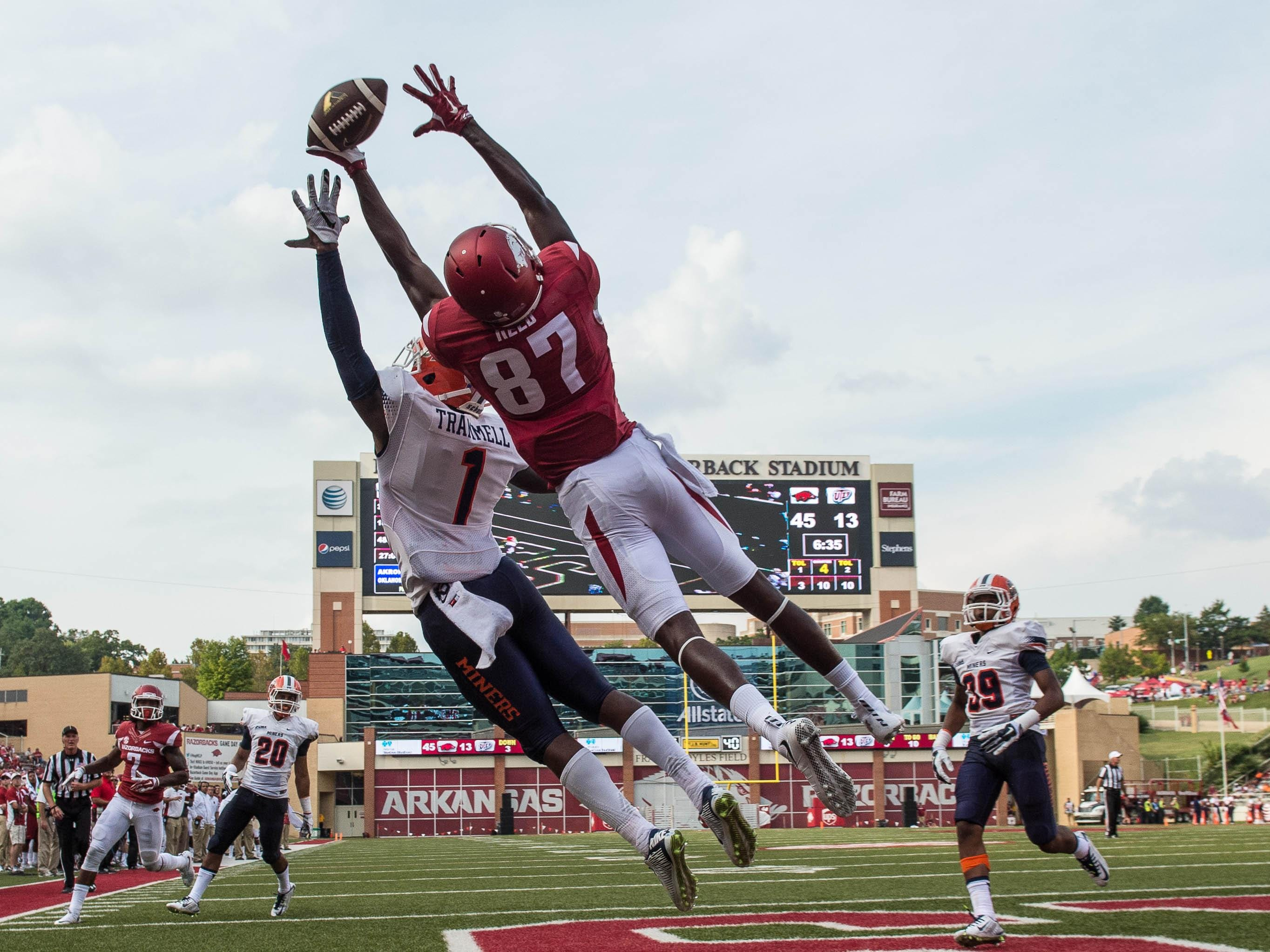 UTEP defensive back Trent Trammel (1) and Arkansas wide receiver Dominique Reed (87) leap for the ball in the end zone in a recent game at Donald W. Reynolds Razorback Stadium.