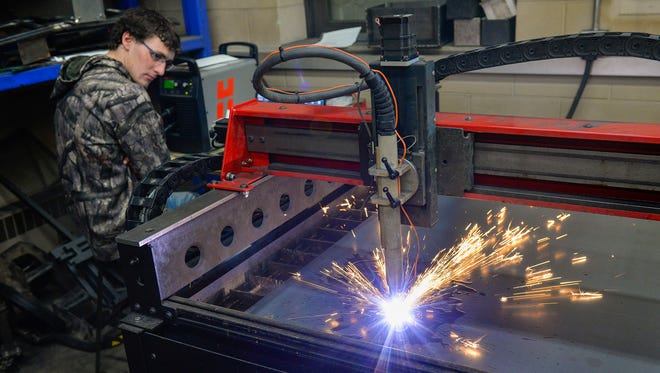 Sitting at a computer, Foley High School senior Collin Schumacher tracks the progress of the computer numerical control plasma cutting table Thursday, April 14, 2016, in the school's metal shop. Students at Foley High School can learn to do computer-aided design projects and get exposure to machines like this one that could land them a future job.