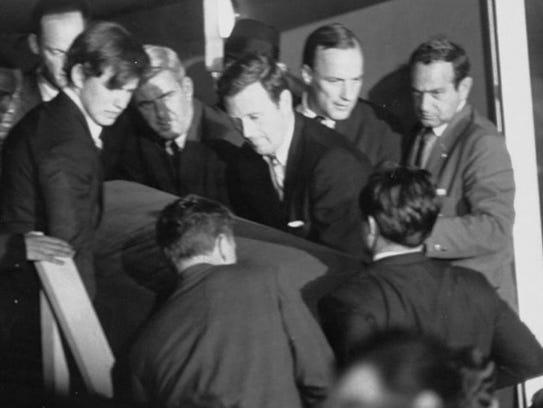 In 1968, John Seigenthaler, center, helps carry the
