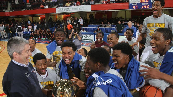 From left, Roman Catalino hands the gold ball to a bunch of excited Mount Vernon players after their 47-39 victory over Spring Valley to win the Class AA boys basketball championship game at the Westchester County Center in White Plains Mar. 2, 2014.