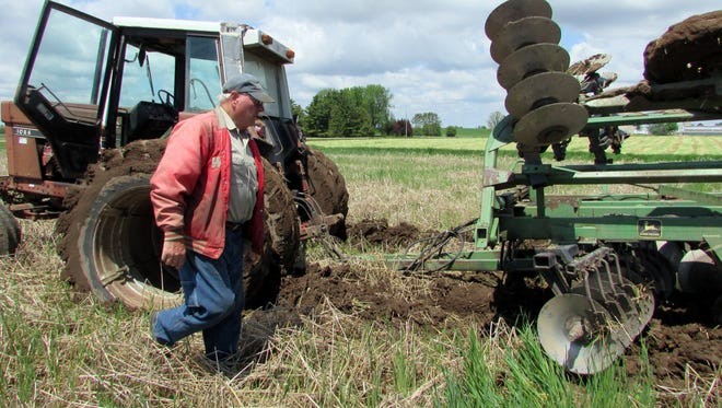Columnist Susan Manzke was on the scene to lend her husband, Bob, a hand when the tractor and disk became stuck in a wet spot.