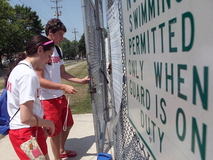 Lifeguards Eric Bradway, 16, and Caroline Madonna, 17, both of Vineland, unlock the gate at the outdoor pool, as the Vineland city pools open, Wednesday, Jul. 2, 2014 in Vineland.  Staff Photo/Sean M. Fitzgerald