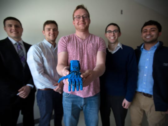 Tue., Feb. 14, 2017:  Derryn Scott, a fifth-year biomedical engineering student at the University of Cincinnati, holds a 3D-printed prosthetic that Enable UC, a student organization, produced. Behind him, are other biomedical engineering students that are part of Enable UC. From left: Nick Bailey, Jacob Knorr, Yosef Kirschner and Ishan Anand.