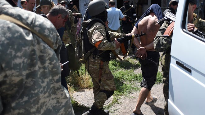 Ukrainian troops from battalion Azov escort to a bus men detained at a site of battle with pro-Russian fighters in Mariupol, in eastern Ukraine, on June 13, 2014.