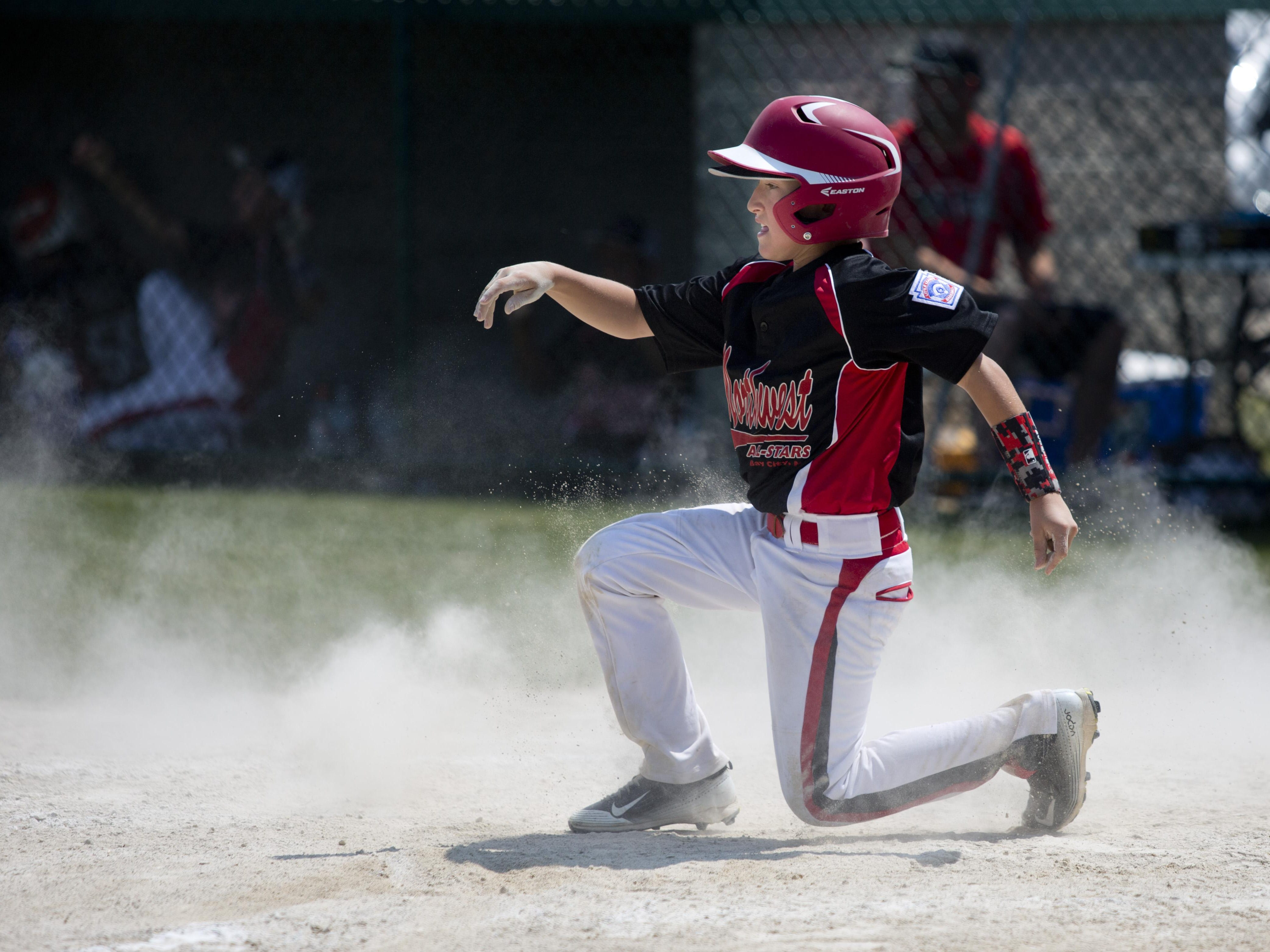 Bay City Northwest's Lucas Julian slides into home to score Wednesday in St. Clair.