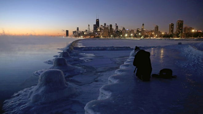 A photographer sets up his tripod on the shore of Lake Michigan before sunrise, Thursday, Jan. 31, 2019, in Chicago.