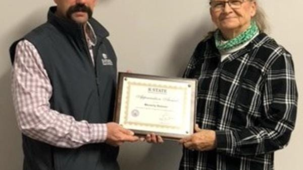 Cade Rensink (left), district director, gives Beverly Seuser, of Salina, a plaque after being recognized by the Central Kansas Extension District Governing Body for the time he has given to the local 4-H Youth Development Program.