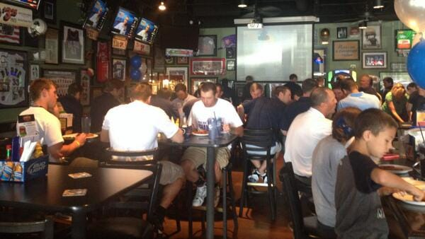 The Xavier baseball team gathers at Champions Grille to await NCAA selection show.