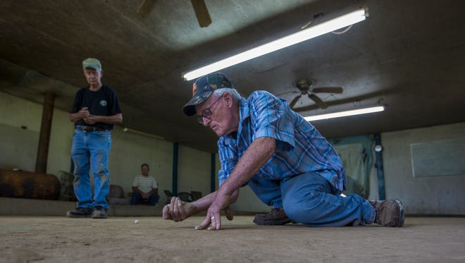 Ernest Hale, 80, gets off a shot during a game of Rolley-Hole at the Monroe County Marble Club Super Dome, in Tompkinsville, Kentucky. June 17, 2017.