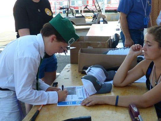 Wyatt Coburn, 12, signs off on his certificate of appreciation