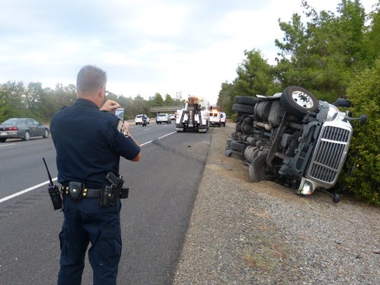 A CHP officer snaps a photo of the overturned big rig.