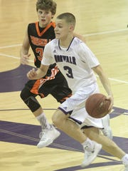 Norwalk sophomore Luke Vaske brings the ball up the court while being paced by Carroll sophomore Cooper Ross. Norwalk beat Carroll 59-58 on a final minute shot by senior Matt Guessford in a Dec. 21 home game.
