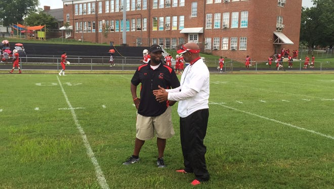Rossview head coach Ron Lambert (right) and East Nashville coach Brian Waite talk during their teams' warmups prior to the start of their season opening prep football game at the TPS Complex Friday.