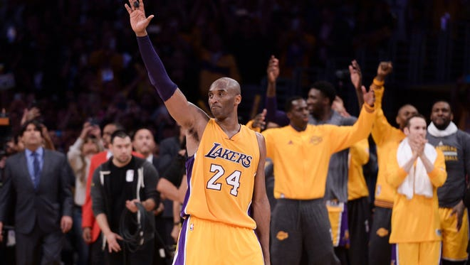 Los Angeles Lakers forward Kobe Bryant waves to the crowd as he heads to the bench before the end of the Lakers win over the Utah Jazz late Wednesday night. Bryant went out in style, scoring 60 points in the final game of his career.
