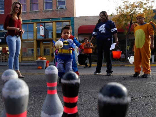 Ethan Randall-Frank prepares to roll a pumpkin on Monday during a bowling game hosted by the Farmington Parks, Recreation and Cultural Affairs during Boopalooza on Main Street in Farmington.