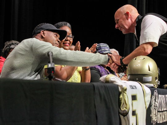 Pendleton High School senior Brad Johnson, left, is congratulated by coach Paul Sutherland, right, near his mother Wendy Johnson, middle, after signing a letter of intent to play for the University of South Carolina football team, on Wednesday, February 1, during an assembly at the school in Pendleton.