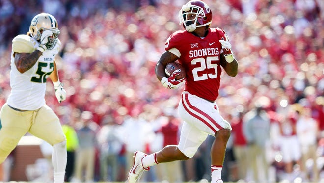 Oklahoma's Joe Mixon runs for a touchdown past Baylor's Greg Roberts during a game last season.