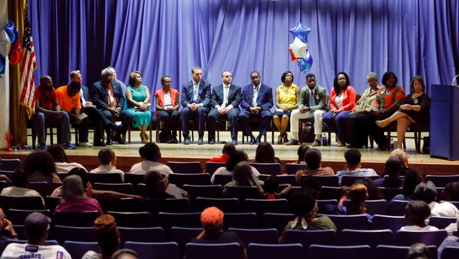 Sixteen candidates fill the stage during a forum for Wilmington city council hopefuls for the third and fourth district seats and four at-large council seats last month at Stubbs Elementary School.