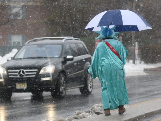 Lisa Johnson of Elmwood Park tries to keep dry from the falling wet snow, as she crosses Boulevard in Elmwood Park dressed as the Statue of Liberty, part of her work day attracting potential clients traveling on nearby Route 4.