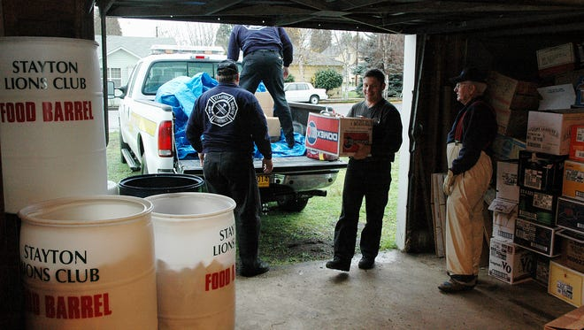 Firefighters Scott Mullen (in truck), Ken Smith (with box), Chief Jack Carriger (back to camera) and Lions Club representative Joe Hallam bring in yet another load of donated goods for the Stayton Food Bank.