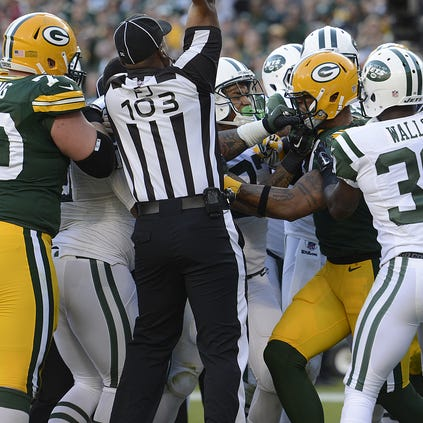 Green Bay Packers tight end Andrew Quarless (81) and New York Jets defensive lineman Sheldon Richardson (91) get into a scuffle at the end of a play in the third quarter during Sunday's game at Lambeau Field.