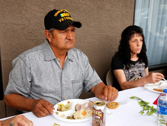 Ronnie Martinez, left, and Vicky Martinez eat a meal provided by the Desert Gold chapter of the Daughters of the American Revolution outside the Farmington Vet Center on Tuesday.