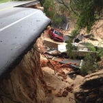 In this now-iconic photo by News Journal photographer Katie King, two cars lie in a pit that was, just a few hours before, a part of Scenic Highway before the raging April floods tore massive chunks of the road away.