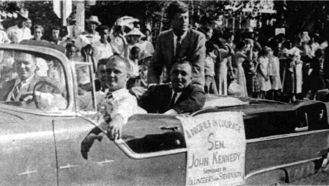 Kennedy rides through downtown Opelousas for the Yambilee Parade .