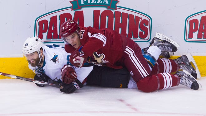 Coyotes' Zbynek Michalek (4) lands on top of Sharks' Brent Burns (88) in the first period at the Gila River Arena in Glendale, AZ on February 13, 2015.