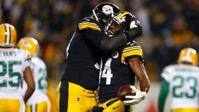 Antonio Brown of the Pittsburgh Steelers celebrates with Maurkice Pouncey after a catch for a two-point conversion in the second quarter during the game against the Green Bay Packers at Heinz Field on November 26, 2017 in Pittsburgh, Pennsylvania.