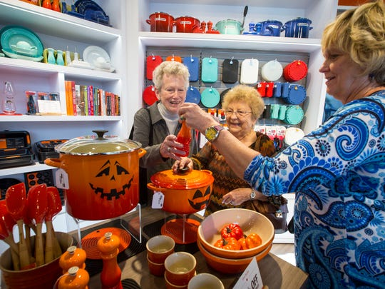 From left, Toni Shivers, Shirley Peyton and Ann Conover look over items at Le Creuset during the opening day at the Outlets of Des Moines in Altoona.
