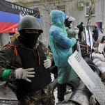 A masked Pro-Russian supporter stands with others during a rally in front of the regional state building in Donetsk, Ukraine, on April 12, 2014.