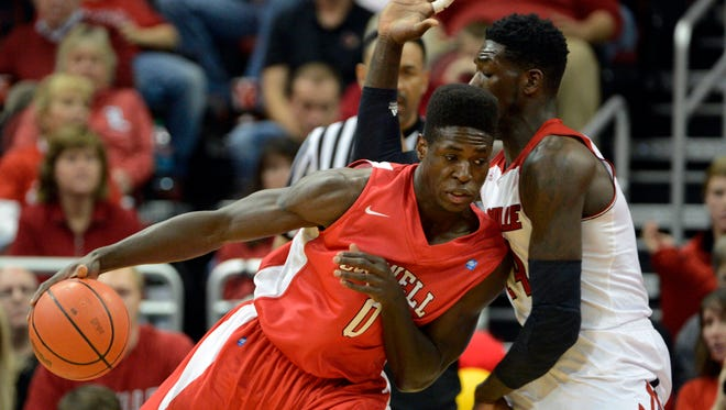Cornell Big Red forward David Onuorah dribbles against Louisville's Montrezl Harrell during the first half of game on Nov 15, 2013, at the KFC Yum! Center in Louisville, Kentucky.
