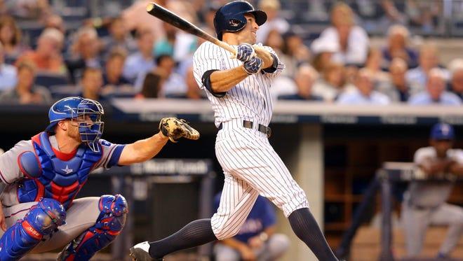 Yankees left fielder Brett Gardner hits a solo home run against the Texas Rangers during the third inning Wednesday at Yankee Stadium.