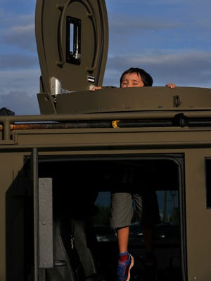 Jaxon Policky, 6, pokes his head out of the turret on the Abilene SWAT Team's Bear Cat, posing for a photo for his mother, Joy. The Abilene Police Department held its annual National Night Out Tuesday Oct. 3, 2017, at the future location of its headquarters, the former Kmart on South First Street.