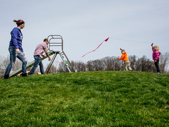 Katie Flenna, Will Osieczonek, Xander Osieczonek, 6, and Kaylie Ceder, 5, fly kits together on a hill during the Community Kite Day Saturday, April 30, 2016, at Pointe Tremble Early Childhood Center in Algonac.