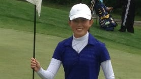 Livonia Stevenson golfer Anna Vento stands next to the pin on the 11th hole at Cattails Golf Course after knocking in her first career hole-in-one.