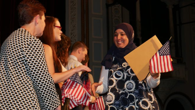 Jahjah Lamyaa walks across stage Friday and is congratulated on becoming a U.S. citizen at a naturalization ceremony at the Bardavon 1869 Opera House in Poughkeepsie.